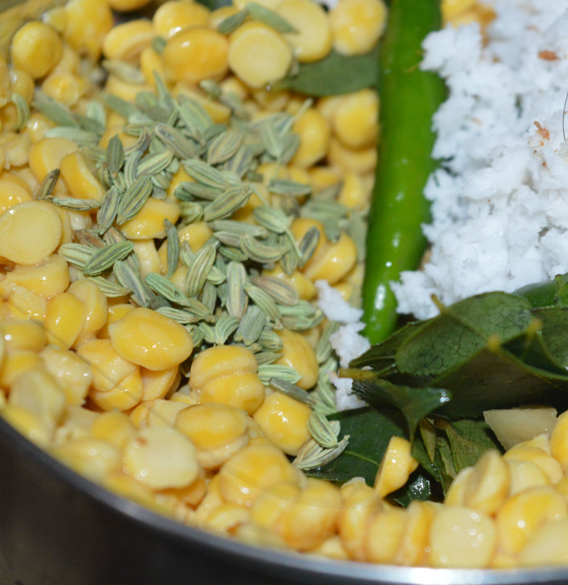 Add green chilies, ginger, garlic, curry leaves, fennel seeds, and grated coconut.