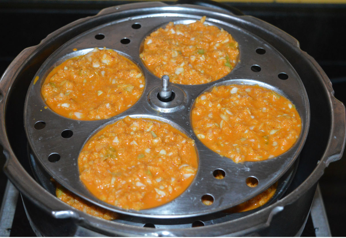 Place the idli stand inside the steamer or cooker. If using a pressure cooker, there's no need to place the weight. Cook over medium-high heat for about 15 minutes. Turn off the heat and open the lid. Take out the idli stand. Allow it to cool.