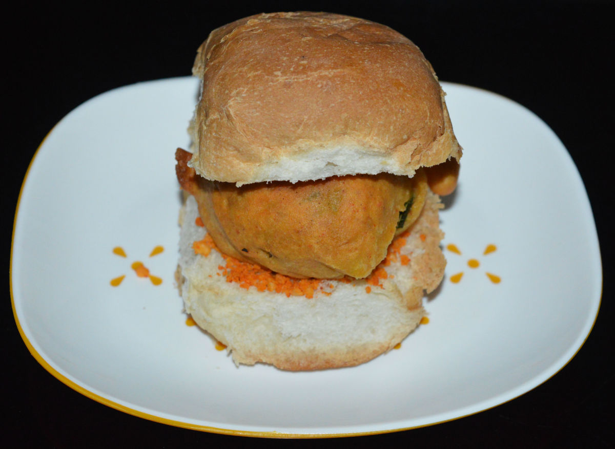 Slit a pav bun horizontally but do not cut all the way through. Spread garlic chutney powder in the slit and then place a potato vada inside.