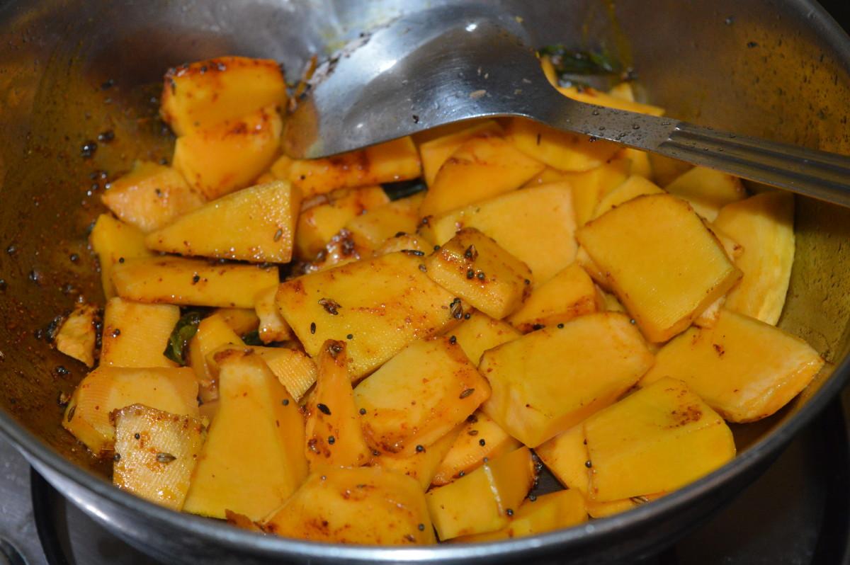 Step 3: Add yellow pumpkin cubes, salt, and sugar. Mix well. Increase heat.