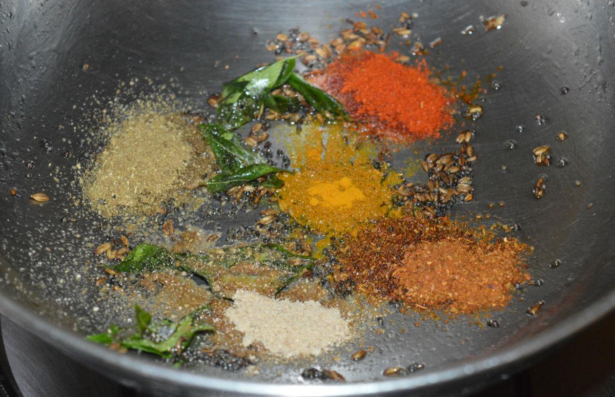 Step 2: Add all spice powders: chili, coriander, turmeric, dry mango, and garam masala. Saute for 5 seconds.