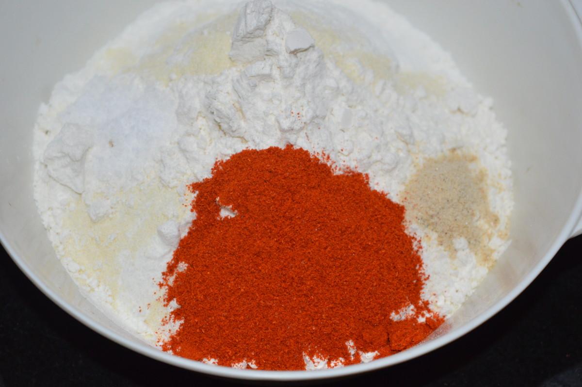 Step 1: In a large mixing bowl, add rice flour, all-purpose flour, semolina, red chili powder, sesame seeds, asafoetida powder, and salt.