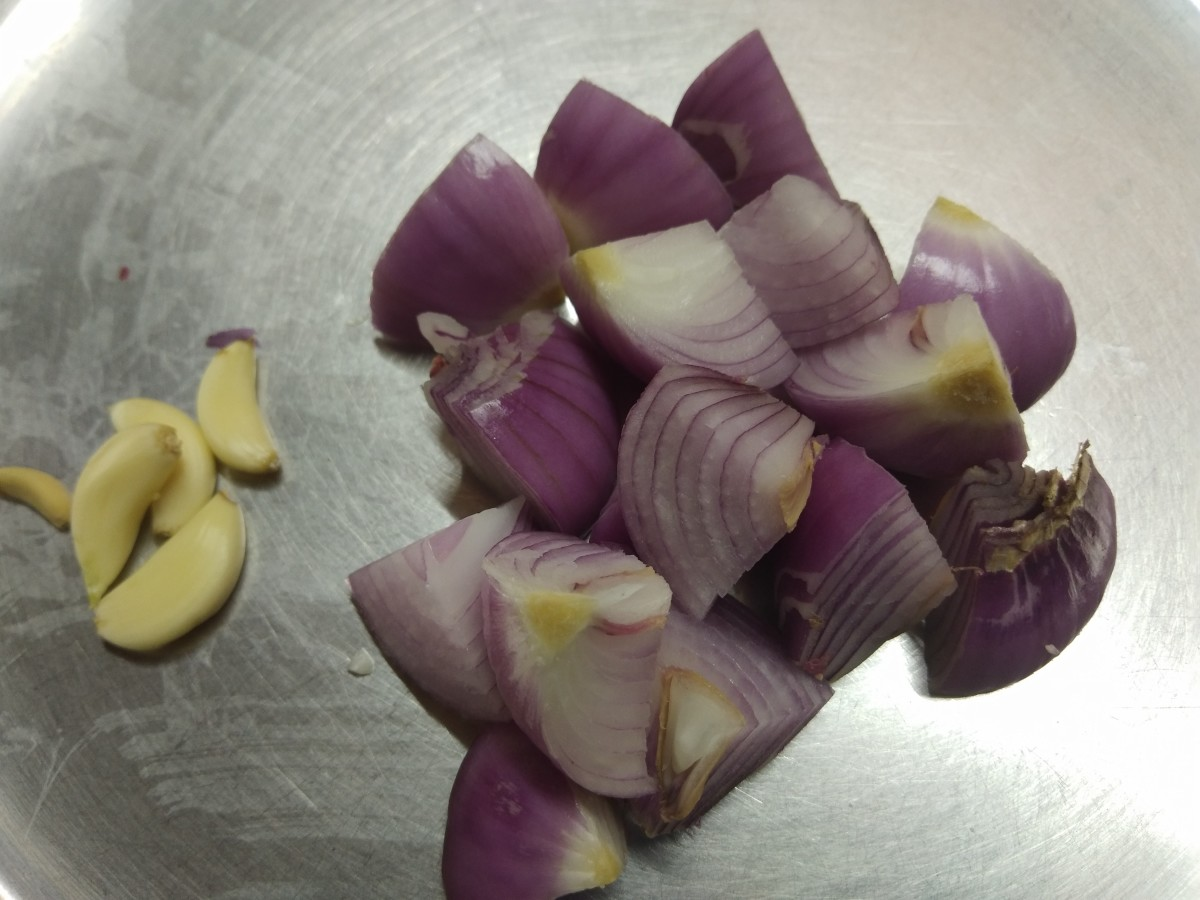Roughly chop the onions and peel the skins off the garlic. Set aside.