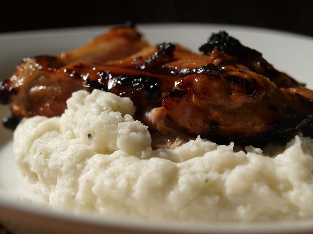 Barbecued chicken on top of mashed potatoes.