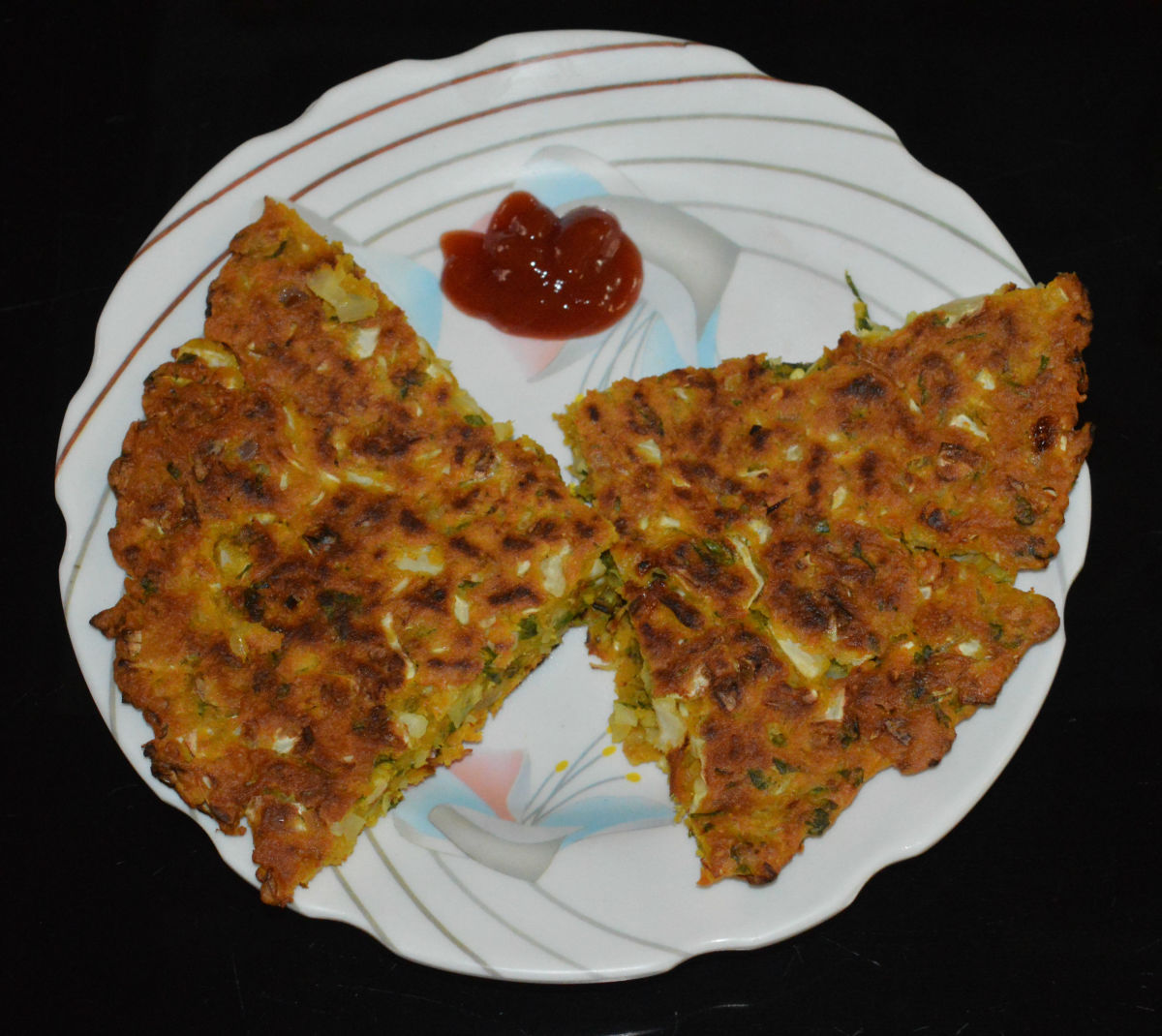 Now, you will get the cabbage pancake on the plate. Cut it in your desired shape. Serve hot with tomato sauce. Enjoy!