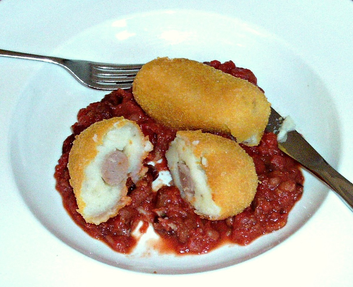 Cocktail sausages in mashed potato deep fried in breadcrumbs, served with beans in tomato sauce
