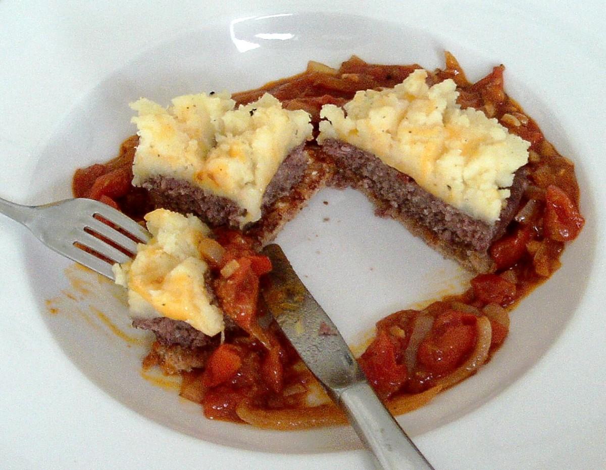 Enjoying buffalo, tomato and basil burger with crispy cheese mash and tomato sauce