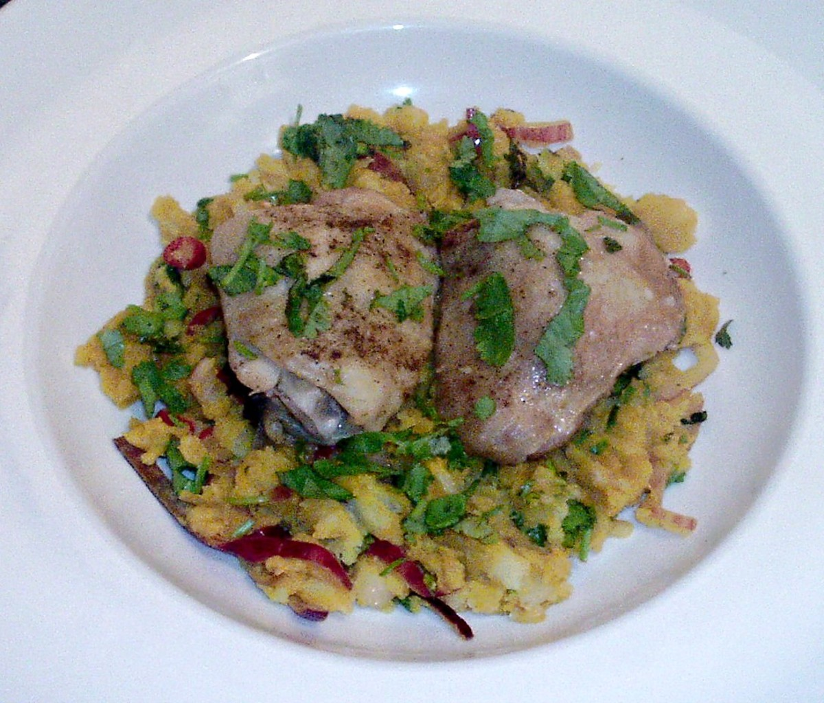 Baked chicken thighs are laid on a bed of curried leftover mash with red onion and chilli