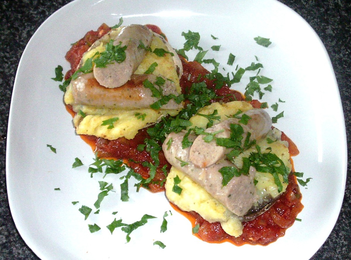 Pork and herb sausages on mashed potato stuffed portobello mushrooms and tomato sauce