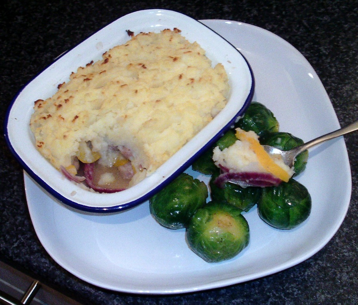 Sausages, peppers and onion topped with mashed potato pie, served with nutmeg spiced Brussels sprouts