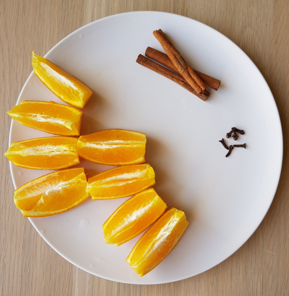 Add flavors: cut oranges, cinnamon, and cloves.