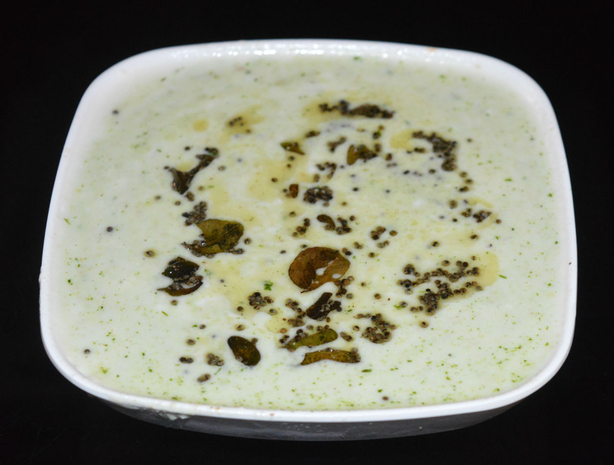 Steps 4 and 5: Heat the oil in a small pan. Add the mustard seeds and curry leaves. Let the mustard crackle. Turn off the heat and transfer it to the bowl containing peanut curd dip. Mix well. Serve this dip with hot thalipeet or paratha.
