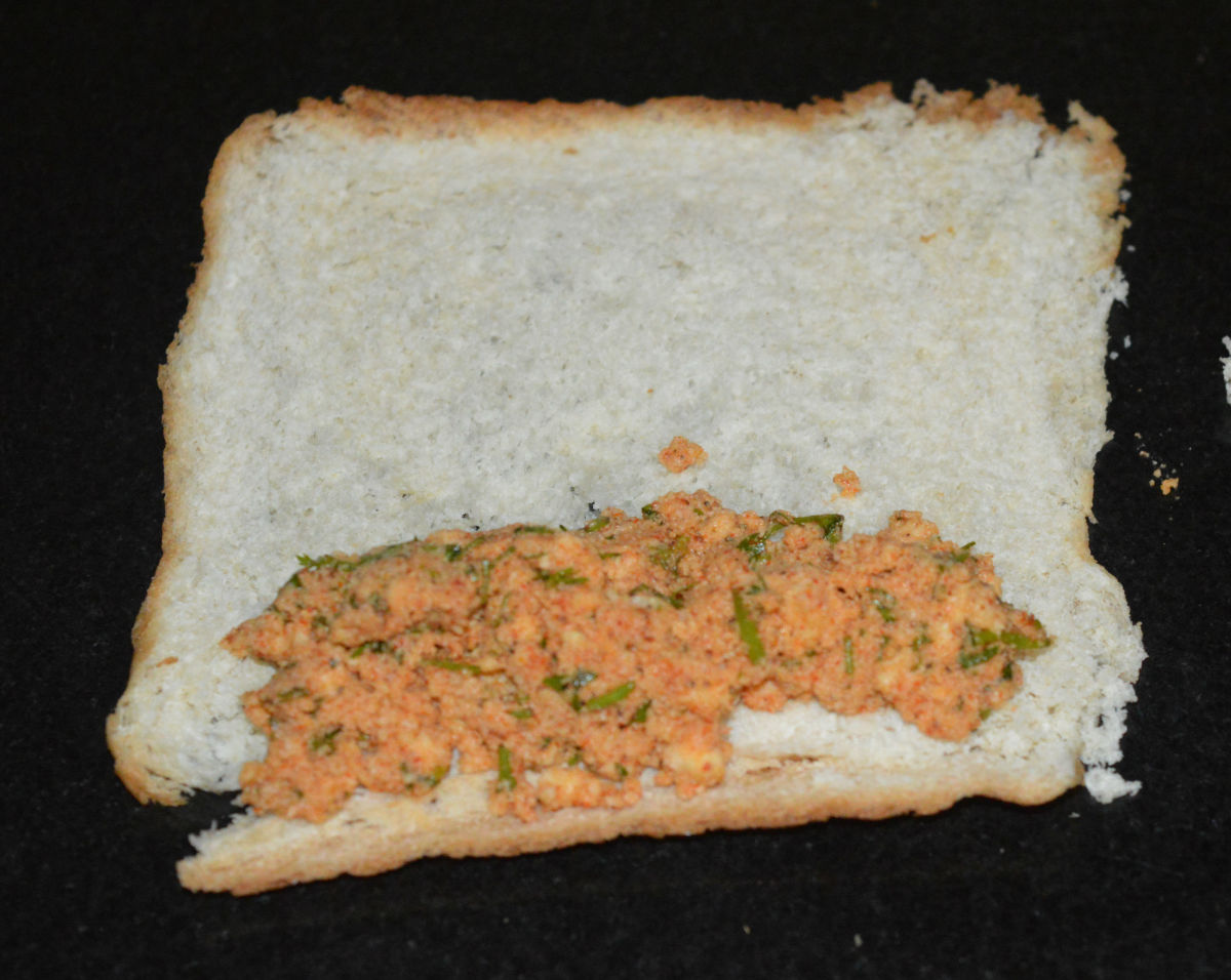 Step three: Place 1 teaspoon of the stuffing on the one edge of the bread. Roll it along with the stuffing to make a roll.