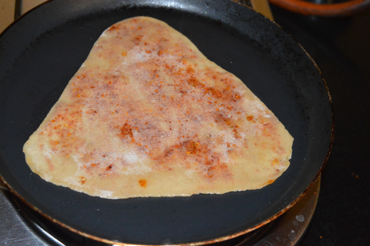 Step five: Cook it on a pan while adding a few drops of oil on both the sides. Let both sides become golden brown. Your favorite spicy paratha is ready!