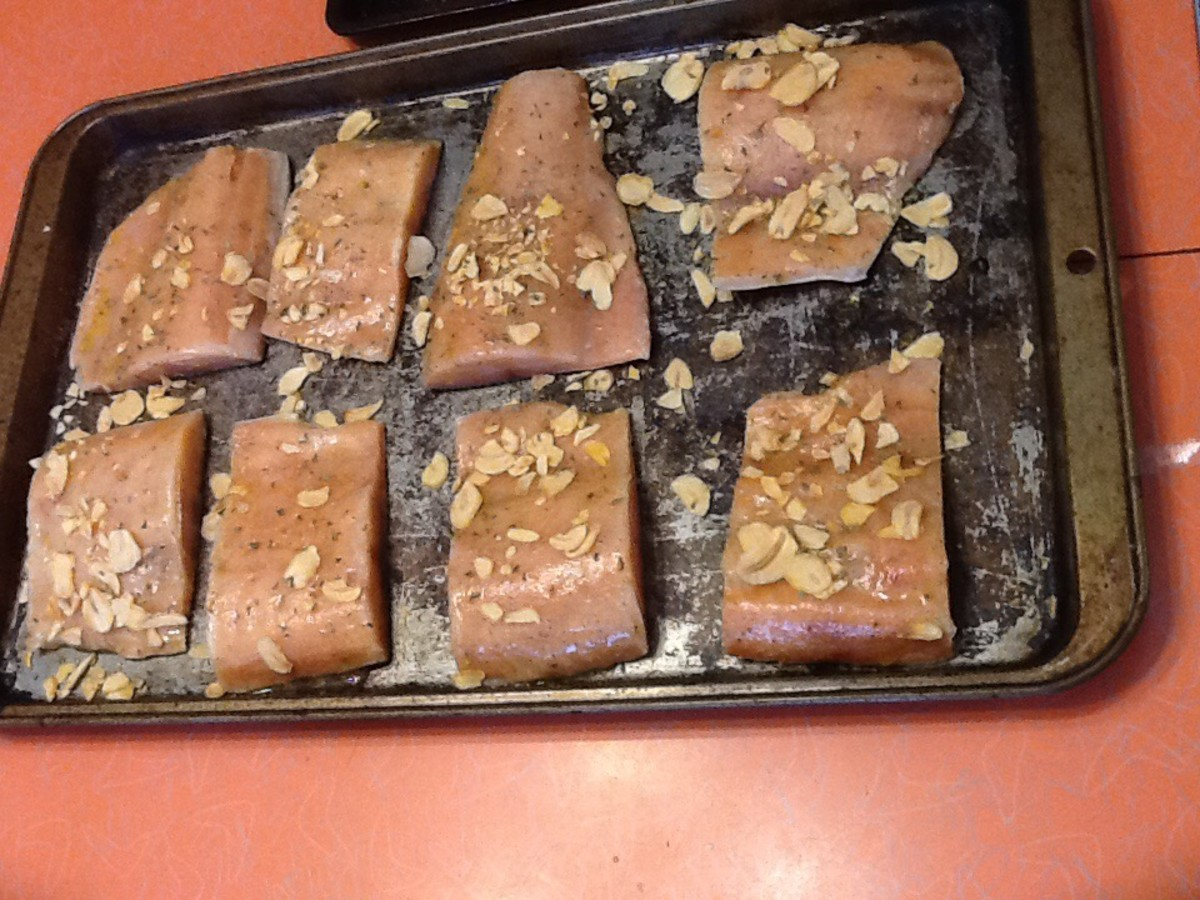 Take a pastry brush and brush the salmon fillets all over with the seasoning. Sprinkle the garlic flakes and parsley on top.