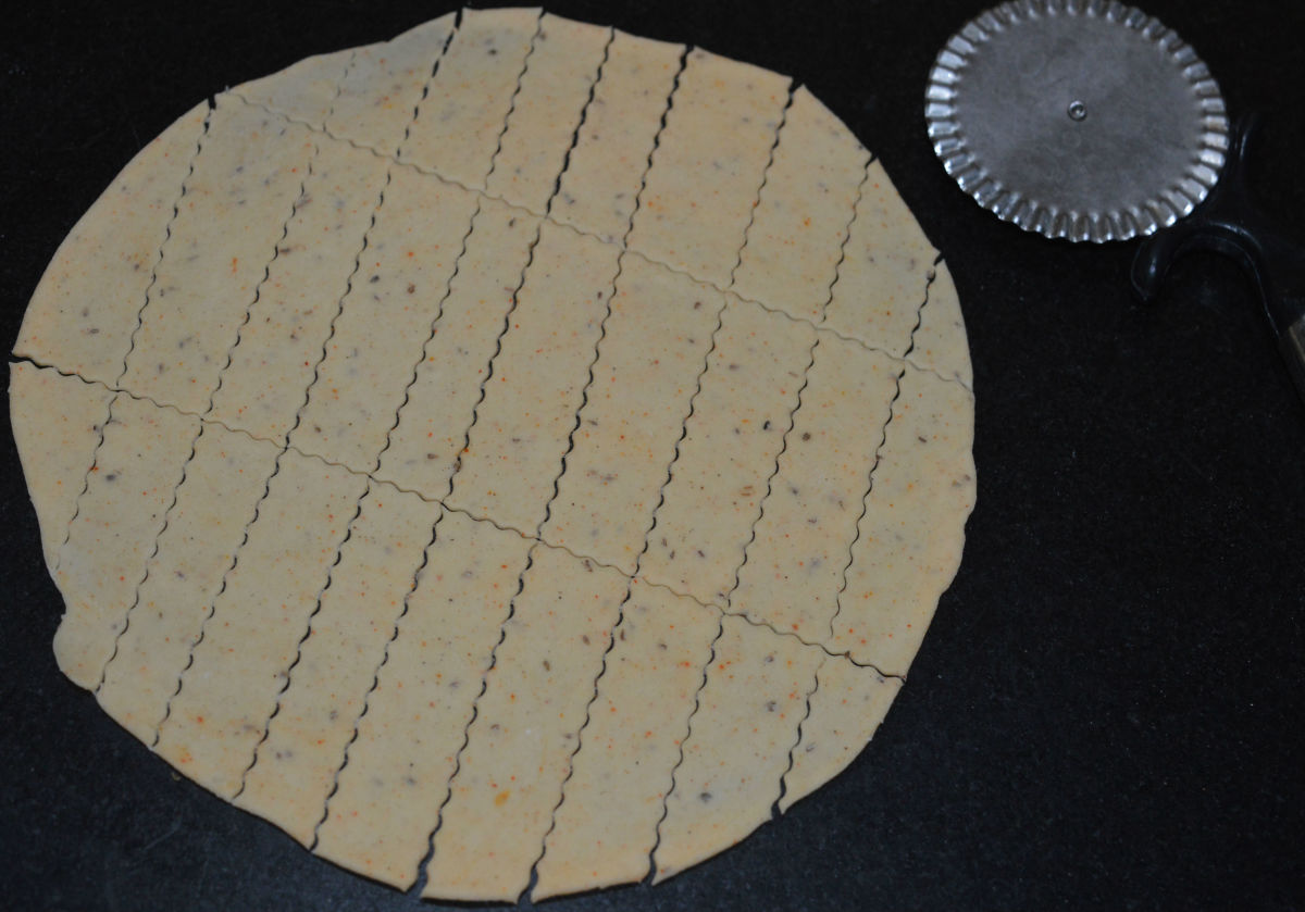 Step two: Take the first dough portion. Make a patty out of it. Roll it out to make a thin disc. With a knife, cut rectangular strips.