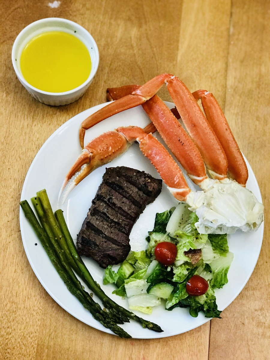 Crab legs with steak, salad, asparagus, and garlic butter.