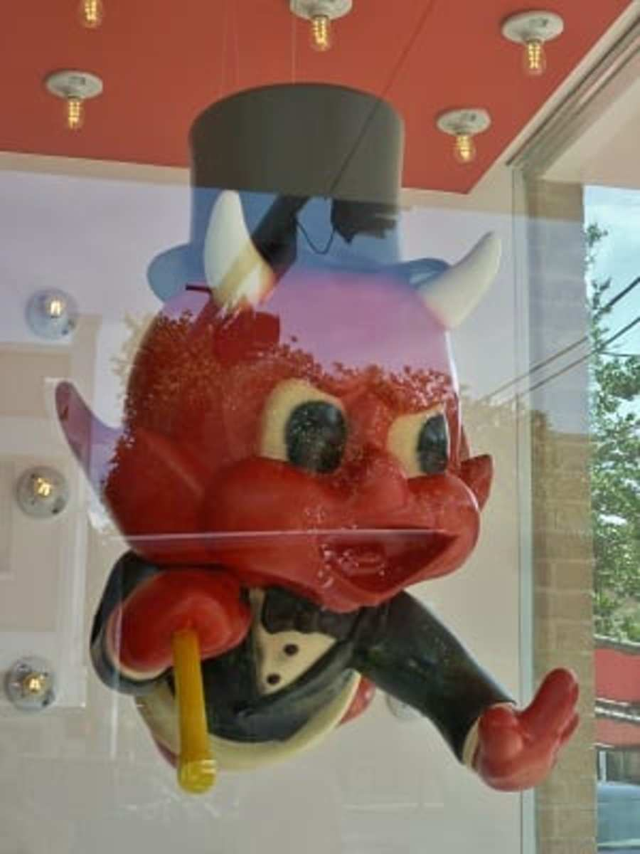 A little red devil stares out the window of the shop