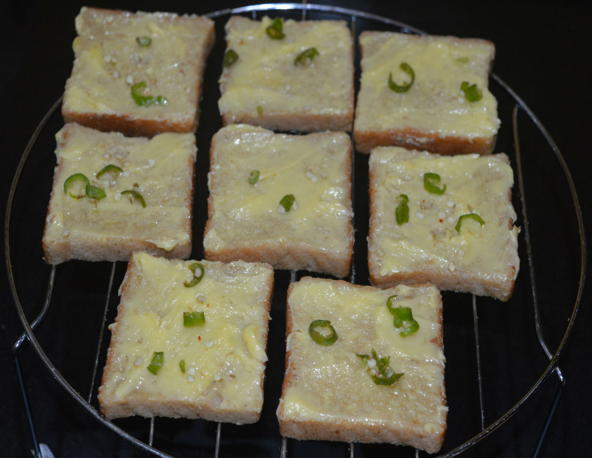 Sprinkle a little bit of salt on all the slices. Add chopped chilies and chopped garlic evenly on the top of all the buttered slices.