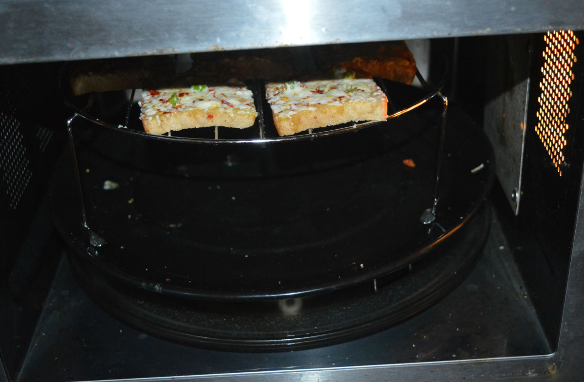 Place the grill stand in the preheated oven. Grill it for 1 minute. Open the oven and check whether the cheese has melted. If not, grill it for some more time, until the cheese melts properly.