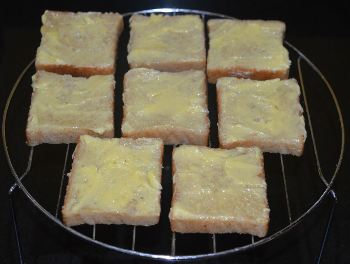 Step two: Take the grill stand out. Apply butter on the top side of all the slices. Arrange them on the grill stand.