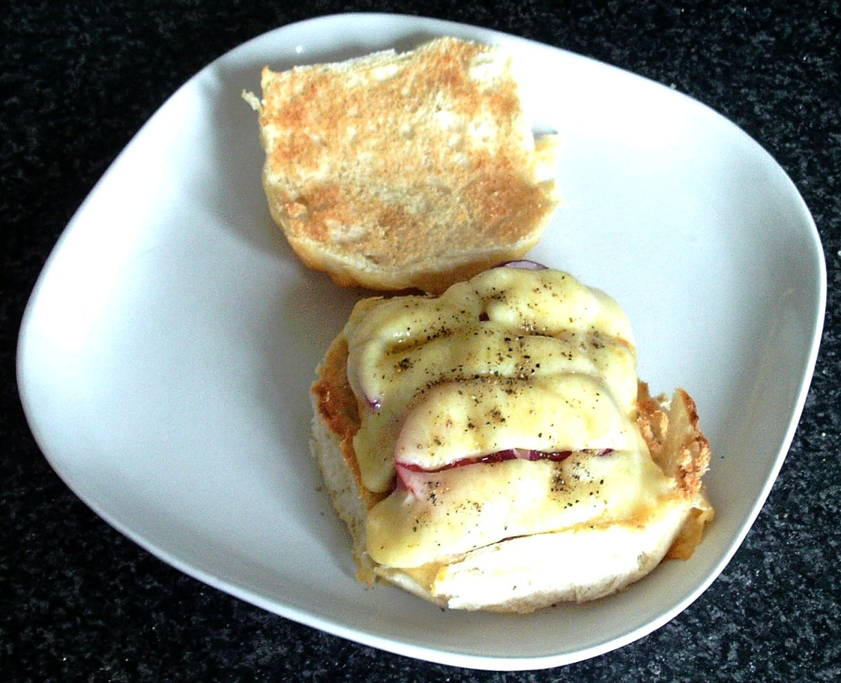 Cheese is melted over corned beef, tomato and onion on a cheese crusted bread roll