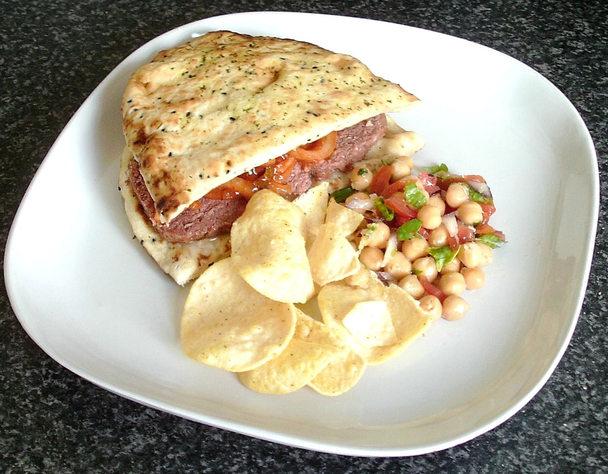 Corned beef and spiced onions naan bread sandwich is served with spicy chickpeas salad and mini poppadoms