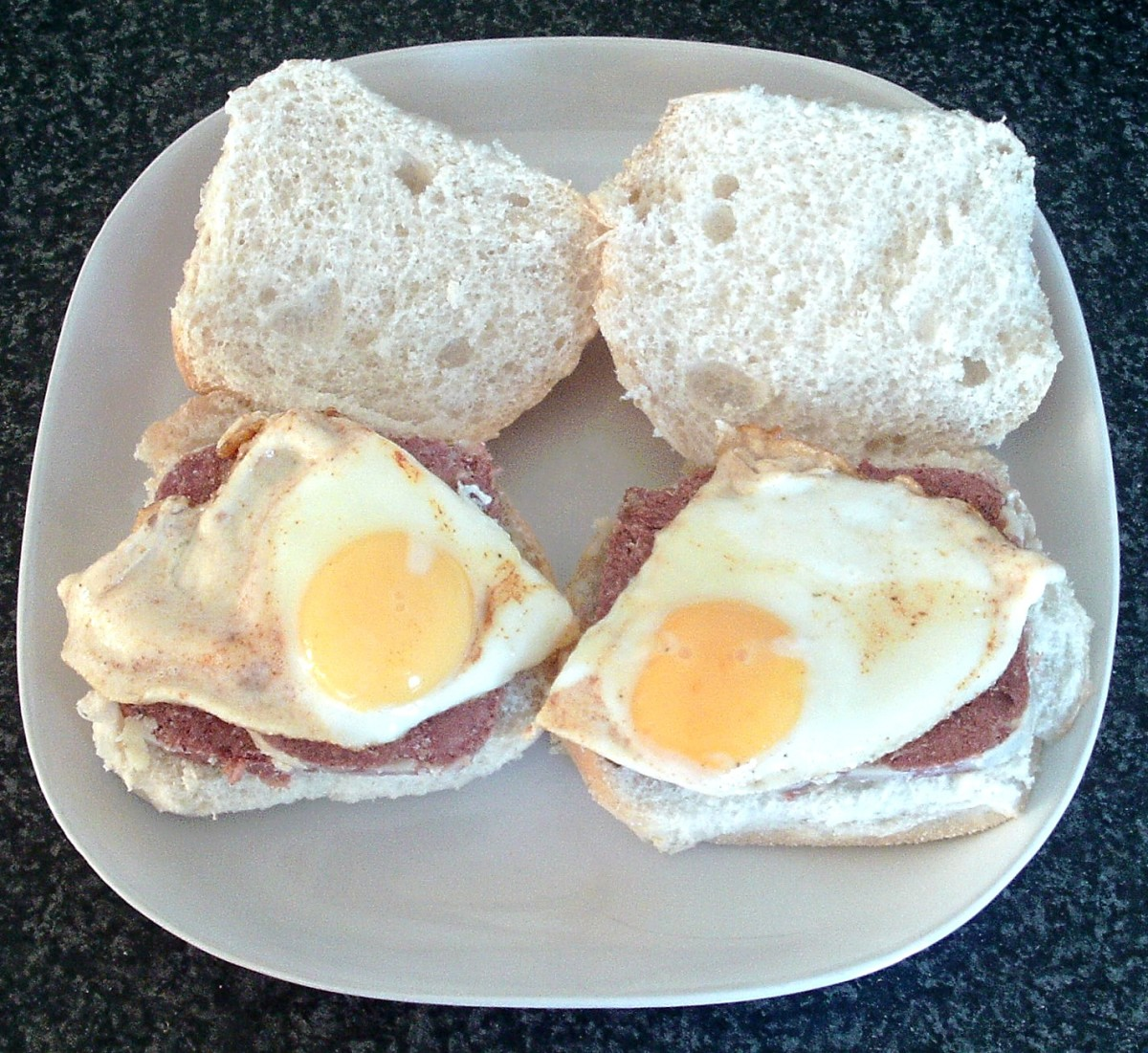 Spiced and sunny side up bread rolls are laid on top of corned beef