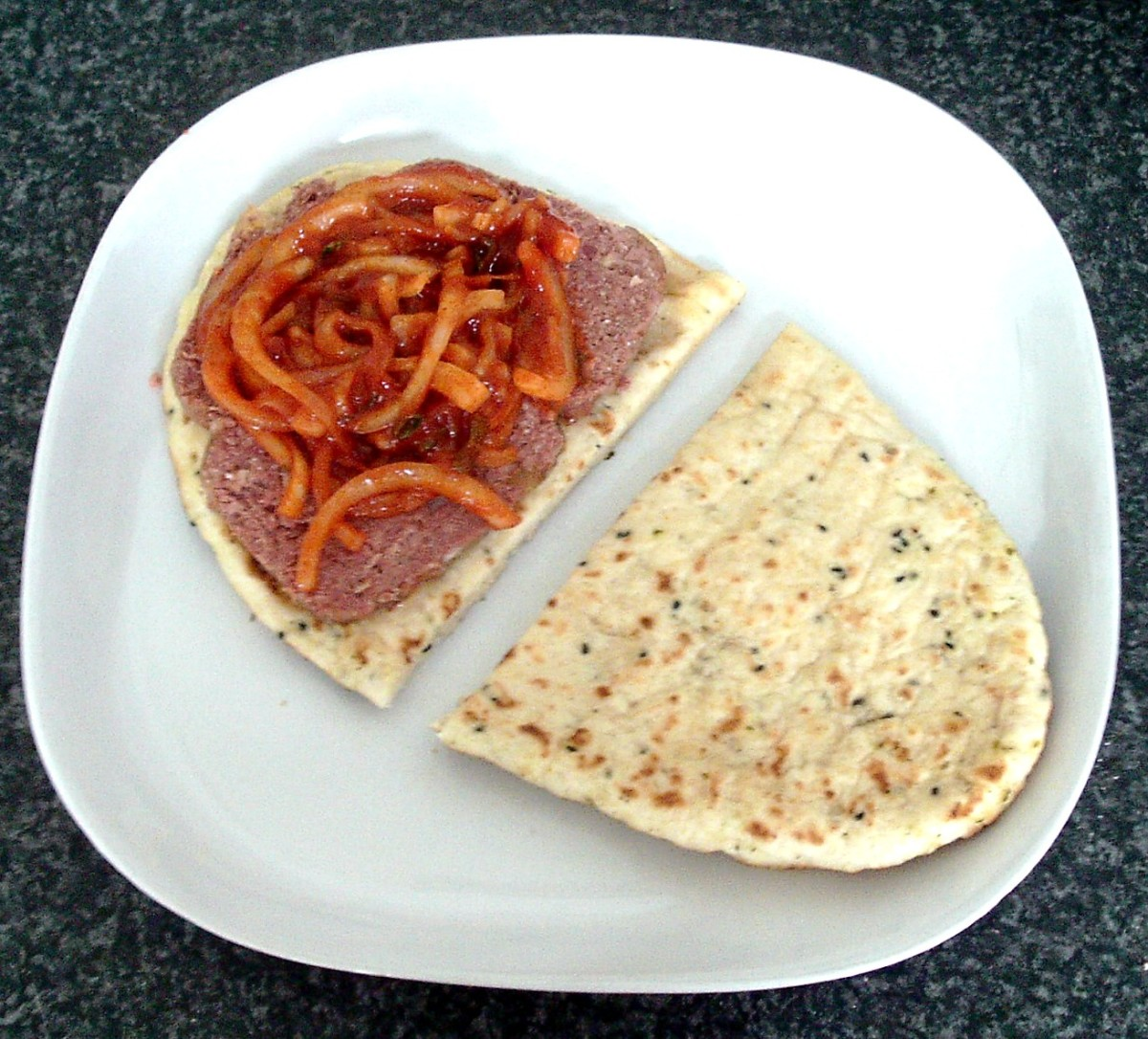 Spiced onions are spooned on to corned beef slices on naan half