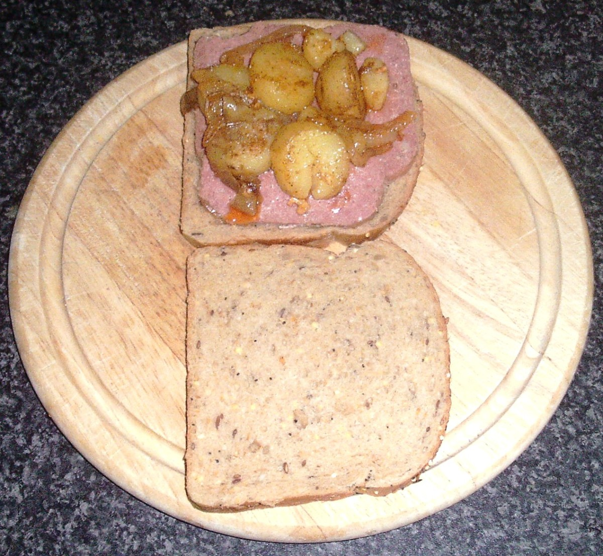 Fried potatoes and onions are arranged on top of corned beef