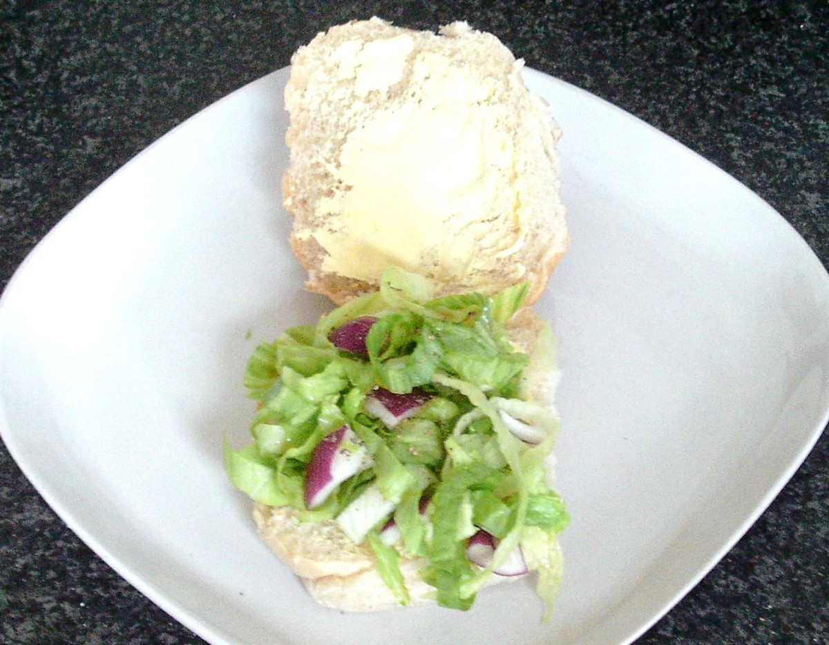 Salad bed is arranged on bottom half of buttered bread roll