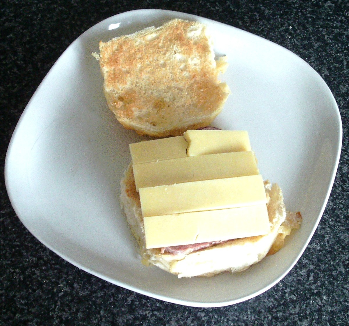Cheese slices are laid over corned beef, tomato and onion