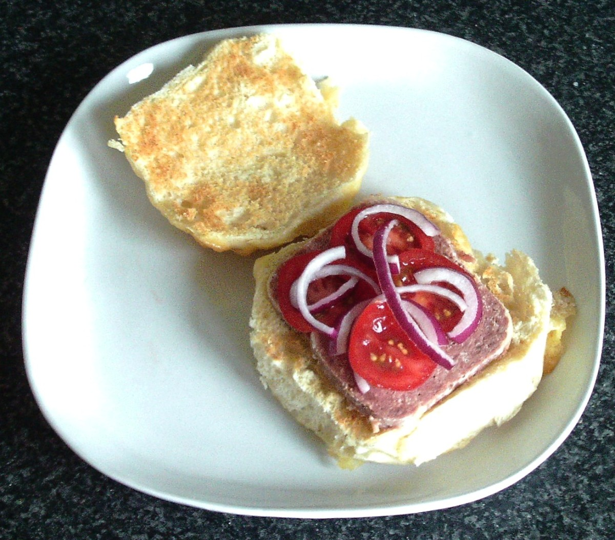 Sliced corned beef, tomato and onion on toasted bread roll