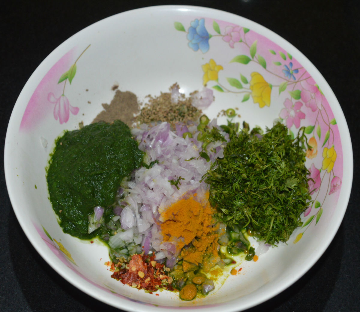 Step two: Add the green paste to a large mixing bowl. Add chopped onions, grated ginger, chopped coriander leaves, green chilies, chili flakes, carom seeds, pepper powder, turmeric powder, jowar flour, and salt.