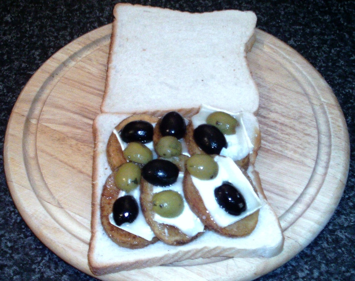 Halved olives are arranged over melted goats cheese and potatoes