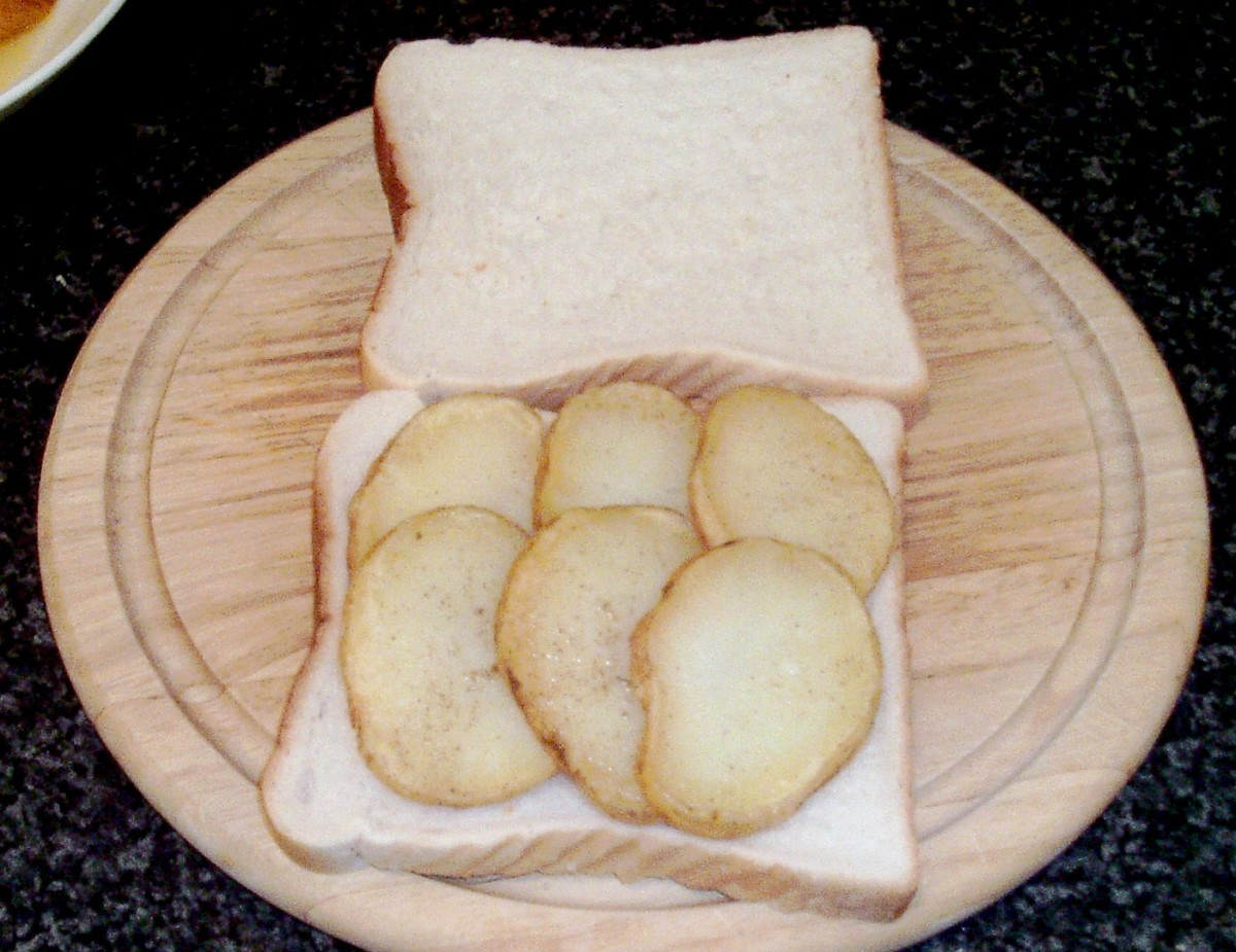 Slices of potato are arranged on one of the slices of bread