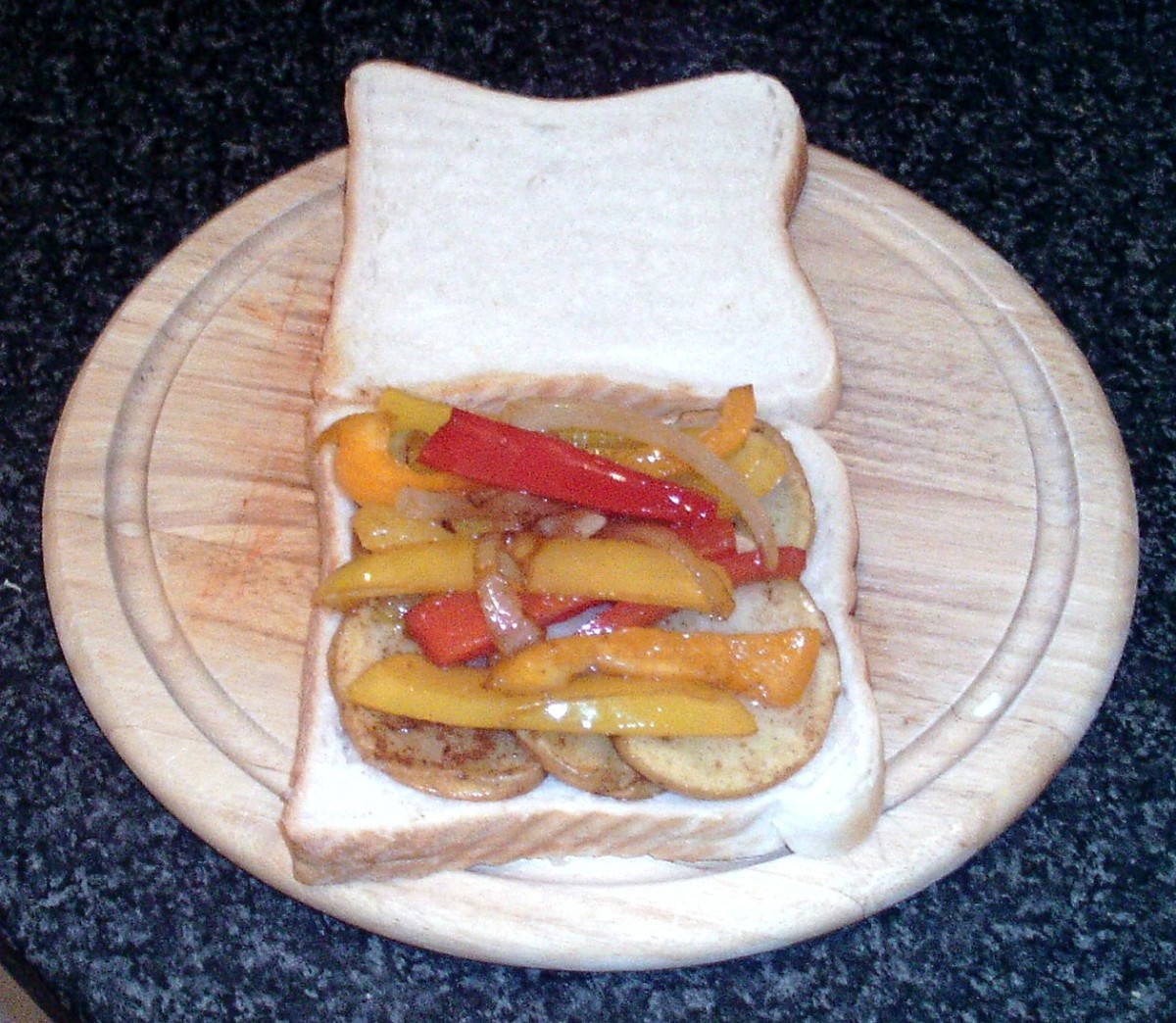 Peppers and onion are arranged on top of potato slices