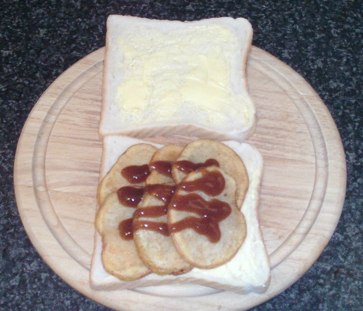Brown sauce is drizzled over potatoes before sandwich is closed over with second slice of bread