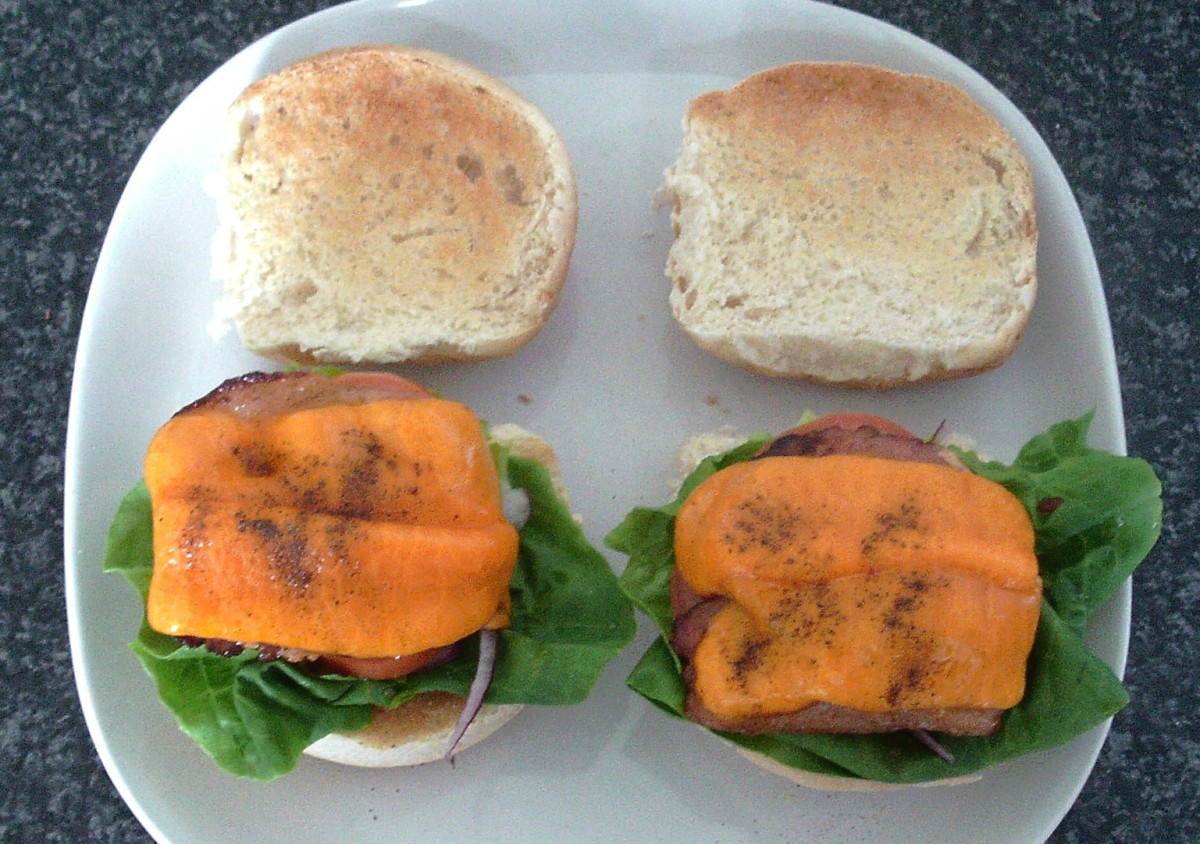 Cheesy bacon is laid on salad beds on the rolls