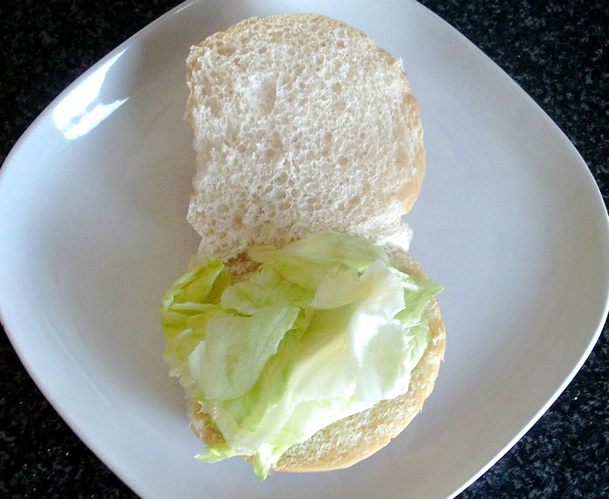 Lettuce bed is arranged on bread roll