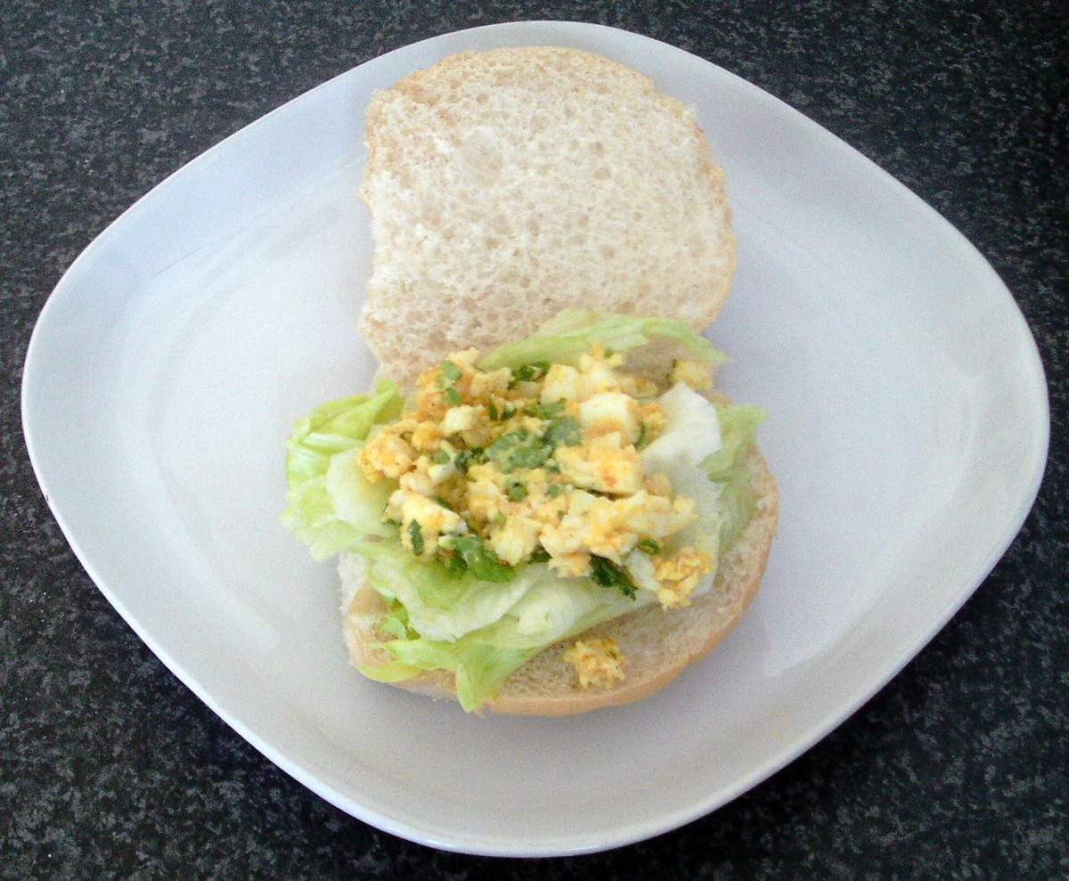 Mashed egg is spread out over lettuce bed