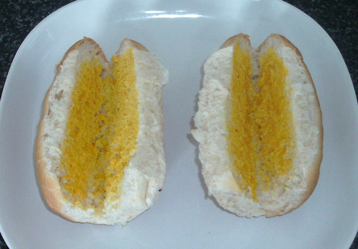 Rolls are cut and spread with mustard