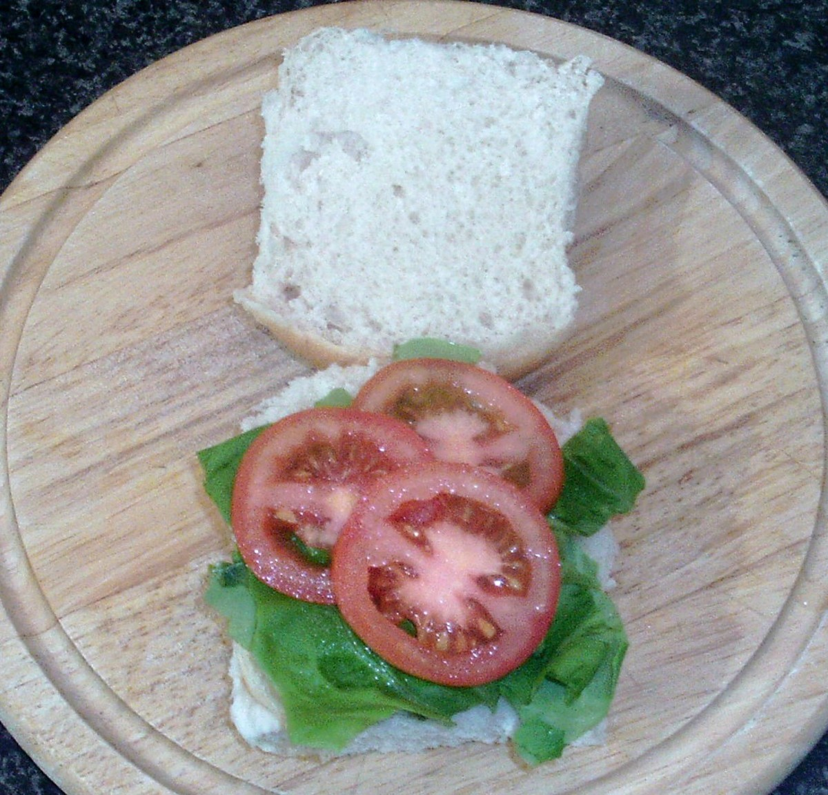 Lettuce and tomato are arranged on roll
