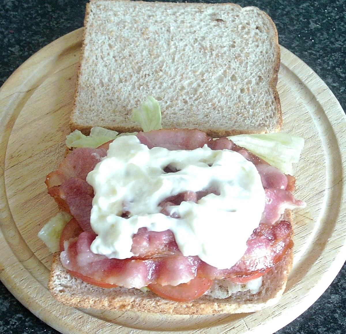 Garlic mayo is spread over bacon