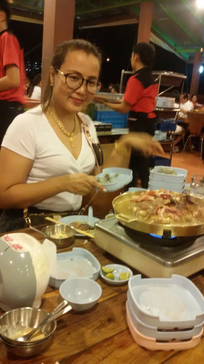 My daughter enjoying Thai barbecue and hot pot at S Barbecue in Udonthani