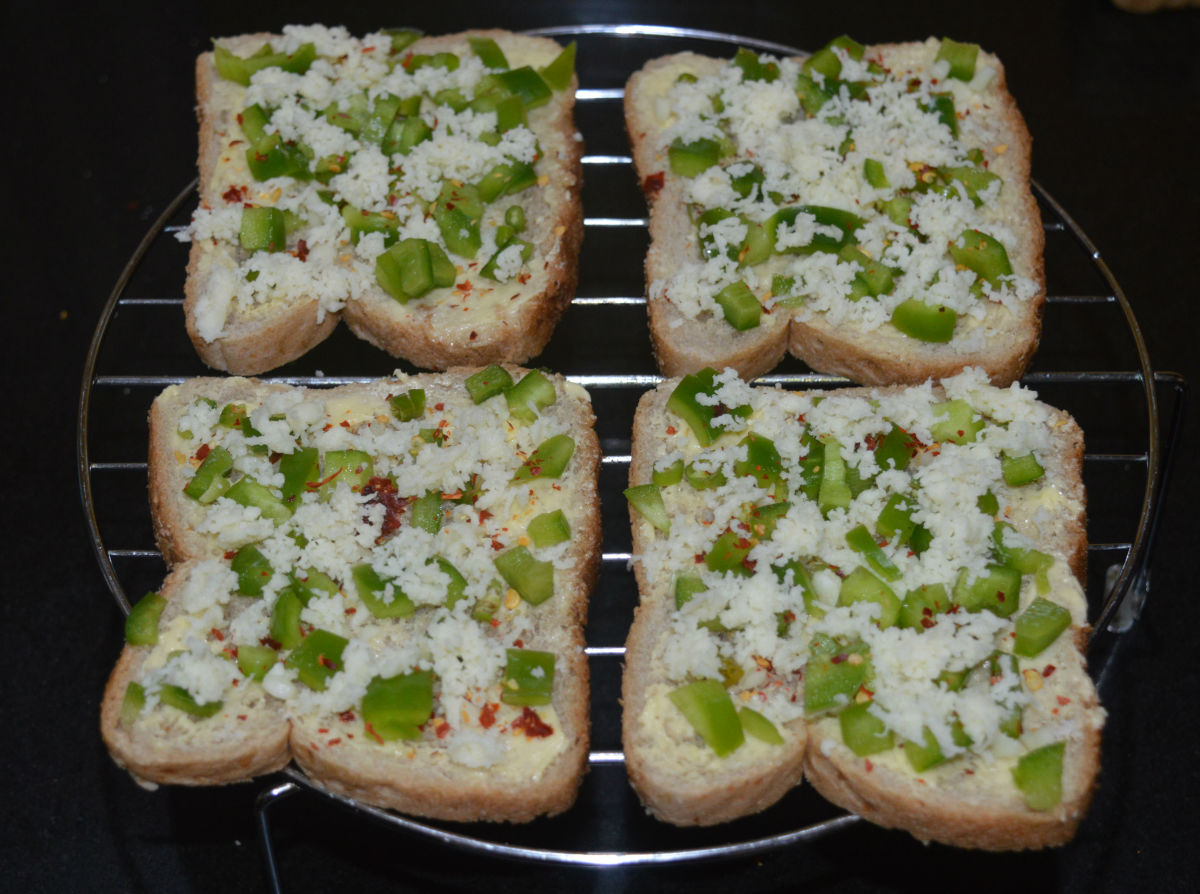 Step two: Spread chopped capsicum on each slice. Next, sprinkle chopped garlic, chopped green chilies, and chili flakes evenly. Spread grated cheese on top and sprinkle a bit of salt.