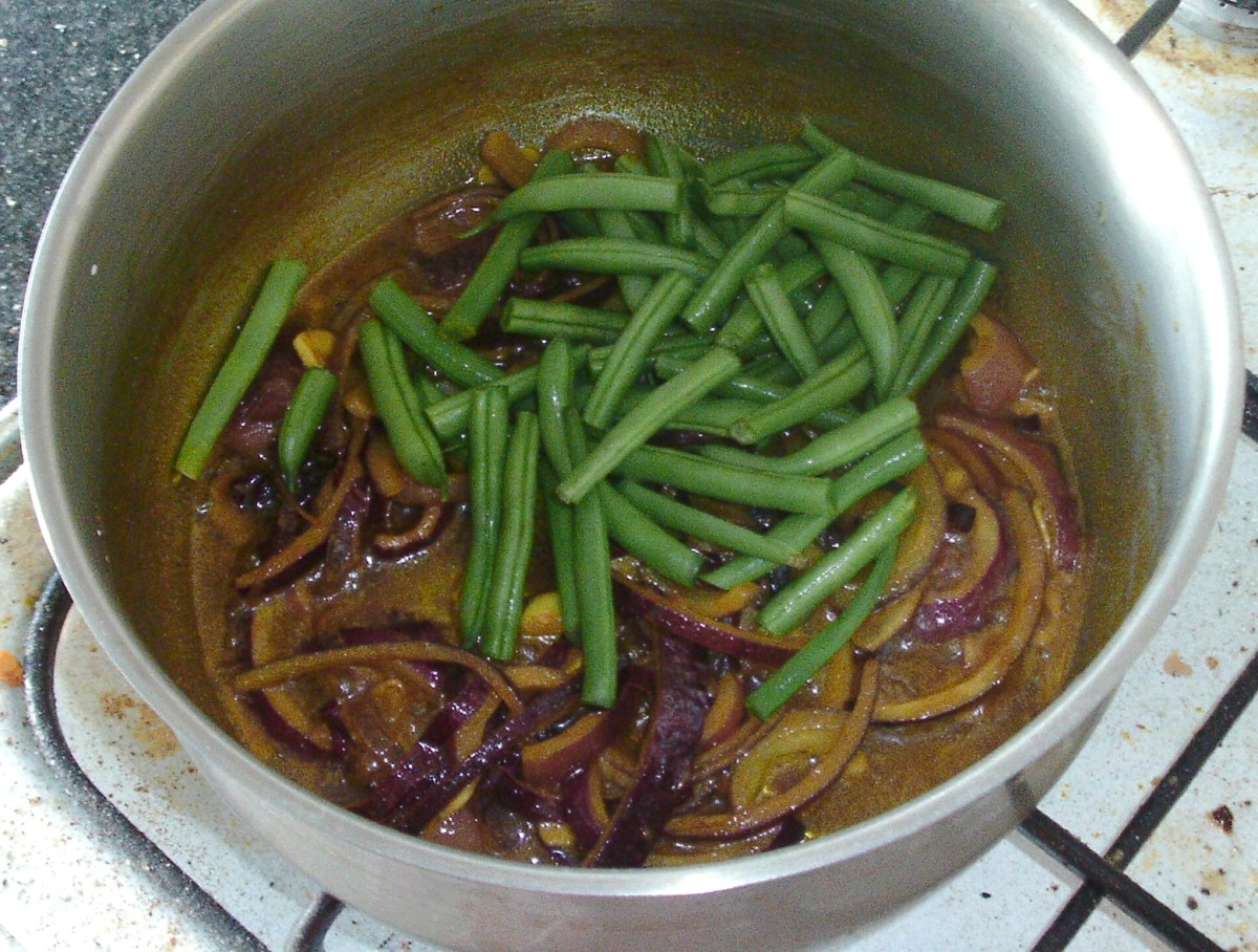 Green beans are added to spiced onions