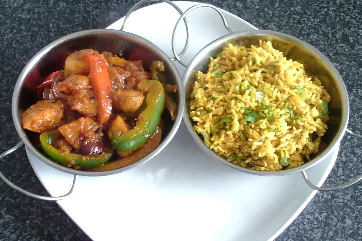 Potato and bell pepper rogan josh and turmeric and coriander rice are spooned in to serving dishes and sat on serving plate