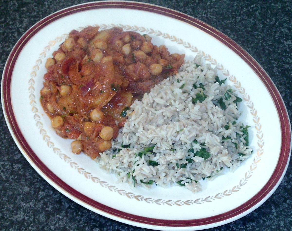 Potato and chickpea curry is served with spinach and garlic brown rice