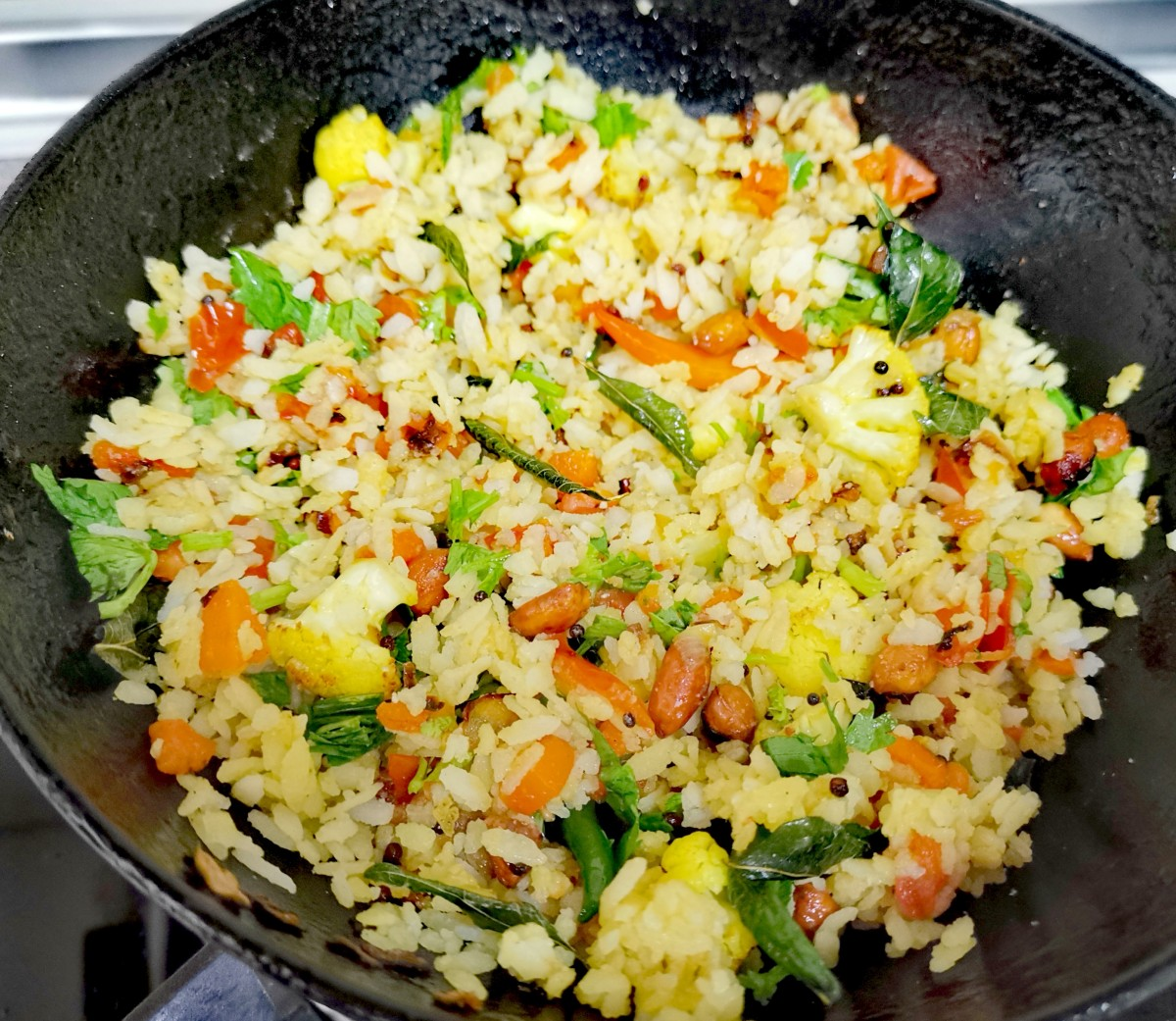 Add washed poha and peanuts. Stir well over medium heat.